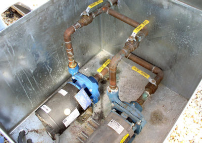 In this photograph, the pump packages have not been correctly installed. Check valves are missing on the pump discharge piping to prevent fluid from flowing through the standby pump (notice the return valve on pump 2 is closed).
